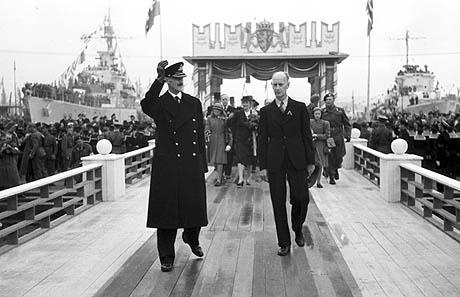 En jublende folkemasse ønsket kongefamilien velkommen tilbake til Norge 7. juni 1945. Her vinker Kong Haakon til folket ved ilandstigningen. Th. ordfører Einar Gerhardsen. (Foto: NTB / Scanpix (kilde: http://www.nrk.no/underholdning/store_norske/4357272.html))